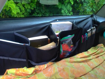$10 Canadian Tire backseat organizers screwed into the car frame organize the ridiculous amount of books I brought.